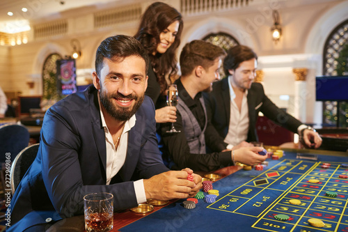 Photo  A man in a suit with a glass of whiskey sitting at table roulette playing poker at a casino