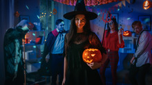 Halloween Costume Party: Gorgeous Seductive Witch Wearing Dress Holds Burning Pumpkin. Background: Beautiful Devil, Scary Death, Count Dracula, Zombie Dancing In The Decorated Room