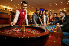 The Croupier Holds A Roulette Ball In A Casino In His Hand.