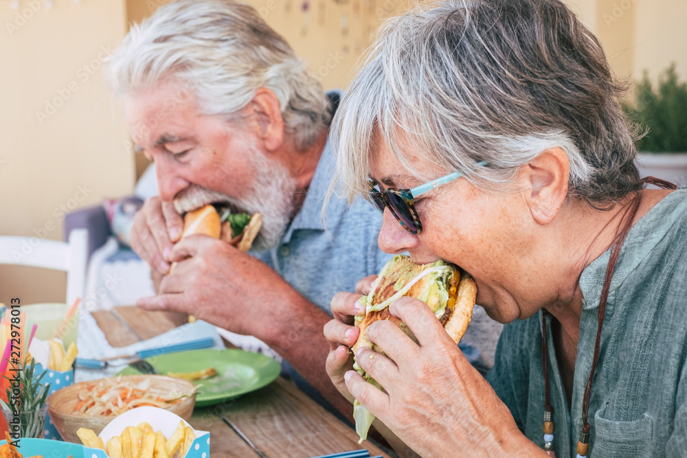 Fototapety, obrazy: People eating hamburger junk food - Couple of senior man and woman with fast food lunch time - close up of elderly no healthy lifestyle - tasty sandwich full of everything