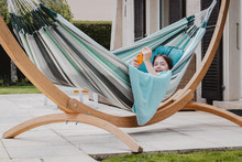 Happy Preteen Girl Lying With Her Smartphone In Hammock Outdoors On Terrace In Garden. Summer Lifestyle. Lazy Week End Or Vacation.