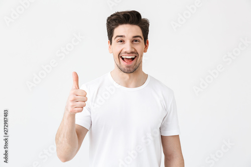 Fotografie, Obraz Excited young man posing isolated over white wall background showing thumbs up gesture