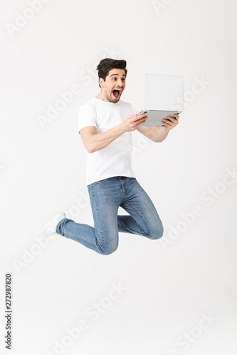 Canvas Prints Textures Happy excited young man posing isolated over white wall using laptop computer jumping.