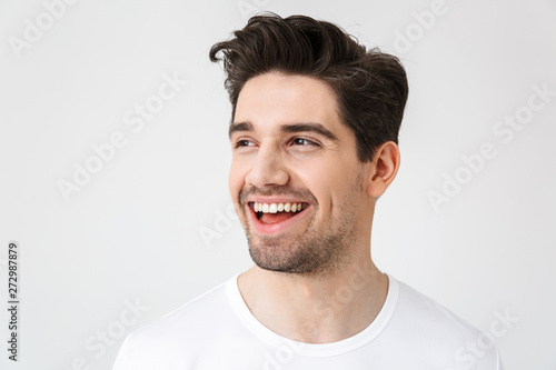 Obraz na plátně  Happy young excited emotional man posing isolated over white wall background
