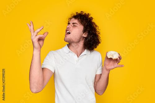 Young man tasting yummy doughnut Canvas Print
