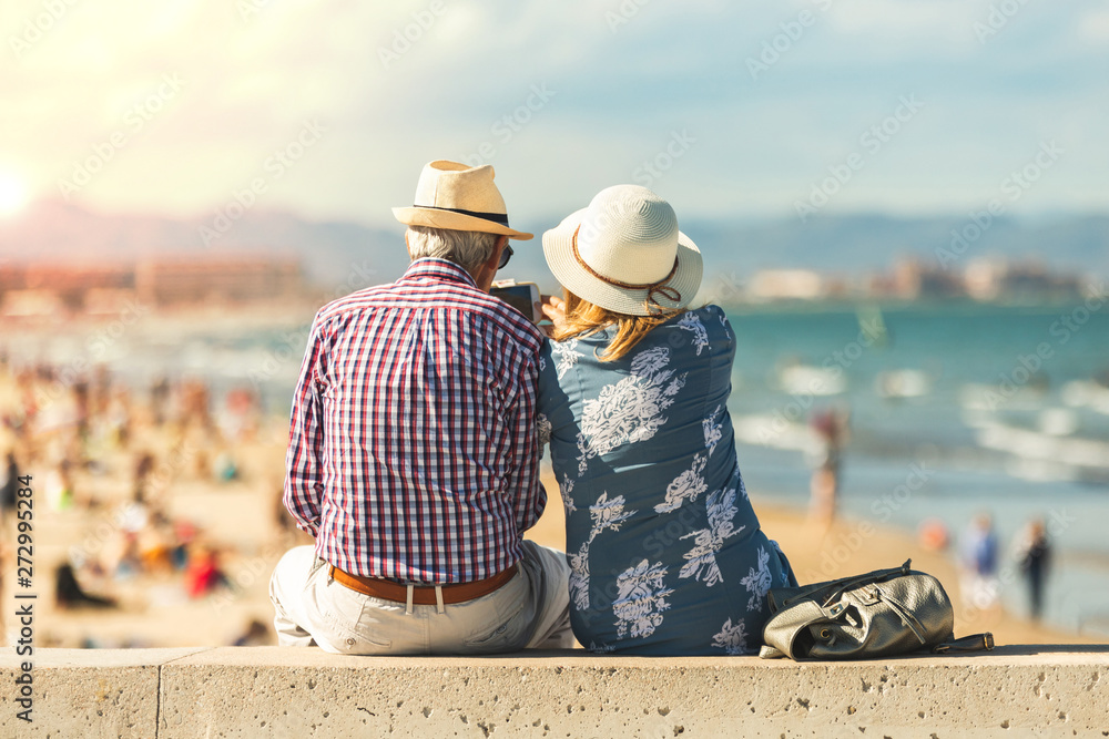 Fototapety, obrazy: Mature couple of retired lovers enjoying retirement on the beach facing the sea with mobile cell phone taking pictures at sunset. Couple happy true love in the nature