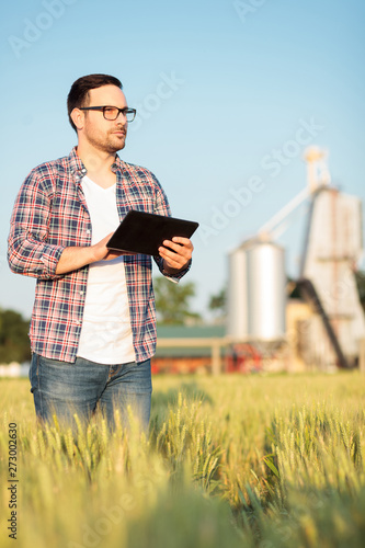 Fototapeta Serious young farmer or agronomist inspecting wheat field before the harvest. Working on a tablet. Grain silo in the background. Organic farming and healthy food production obraz