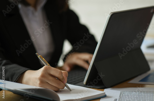 Fototapety, obrazy: Businesswomen are using laptop and taking notes of work on the desk in the office.