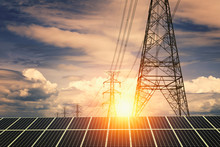 Solar Panels With Electricity Pylon And Sunset. Clean Power Energy Concept..
