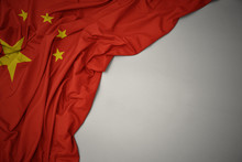 Waving National Flag Of China On A Gray Background.