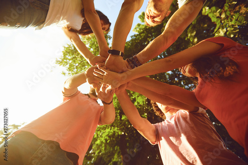 Foto  Friends hold hands in the park in the summer.