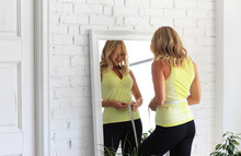 Stay In Shape. Young Woman With Athletic Body Measures Her Waist With A Measure Type In Front Of A Mirror.