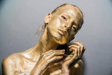 Fashion Model Woman Golden Skin Face In Bright Sparkles, Trendy Glowing Gold Skin Make-up. Glitter Metallic Shine   Makeup