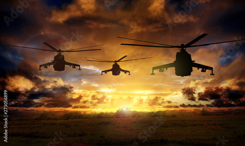 Leinwand Poster Helicopter silhouettes on sunset background