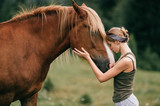 Young beautiful girl hugging horse at nature. Horse lover.
