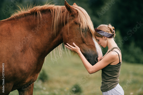 Young beautiful girl hugging horse at nature. Horse lover. Wallpaper Mural