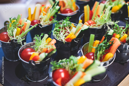 Fototapeta Beautifully decorated catering banquet table with variety of vegetables and different vegan vegetarian snacks on corporate christmas birthday party event or wedding celebration obraz