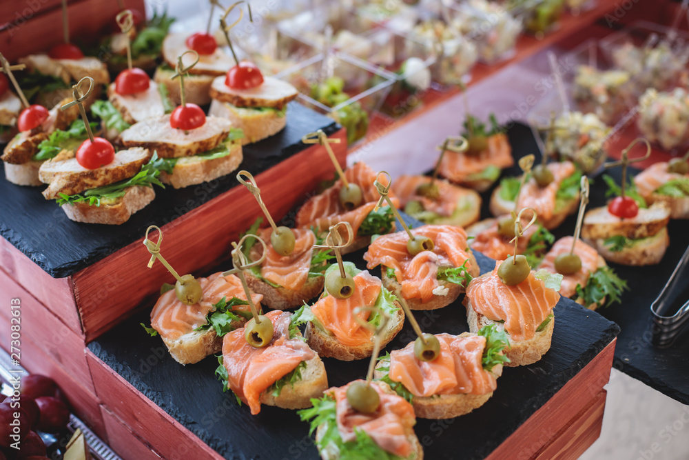 Fototapeta Beautifully decorated catering banquet table with assortment variety of different food snacks and appetizers on corporate christmas birthday party event or wedding celebration