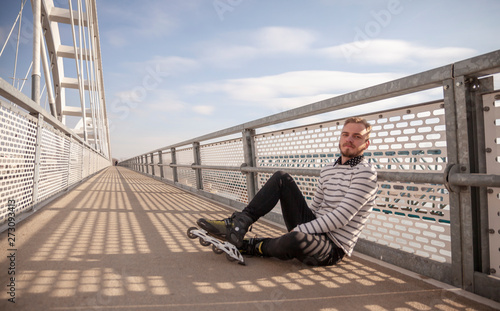 Fotografie, Obraz  one young man, posing, sitting on a bridge wearing inline skates.