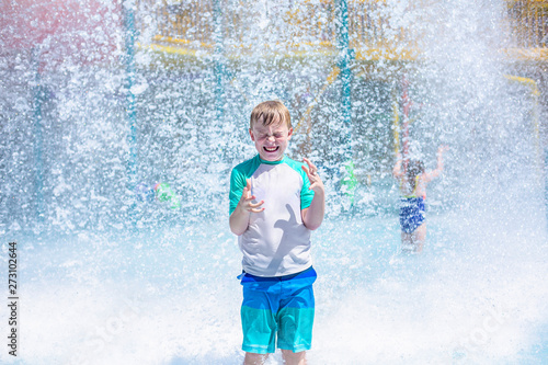 Photo Young boy getting soaking wet while at an outdoor water park