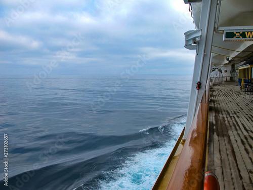 Foto op Plexiglas Arctica Holzplanken auf Bootsdeck von Kreuzfahrtschiff mit Horizont, Meer und Wolken