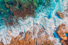 Azure Clear Water Hits The Rocky Coast Of Coral Beach. Aerial Top View