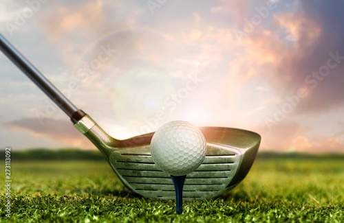 Stampa su Tela Golf club and ball on grass with under sunset sky lights
