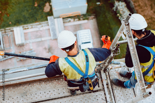 Fototapeta workers work removing a scaffolding at high altitude in Oviedo, Asturias, Spain