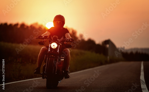 Fototapety, obrazy: Man on motorcycle rides the route during sunset.
