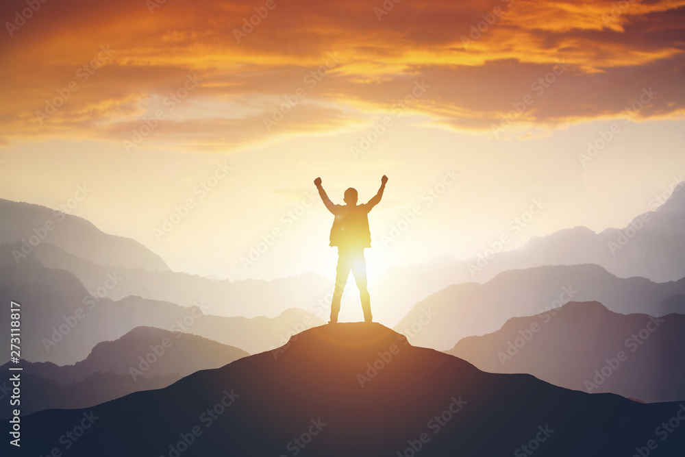Fototapety, obrazy: Man standing on edge of mountain feeling victorious with arms up in the air.