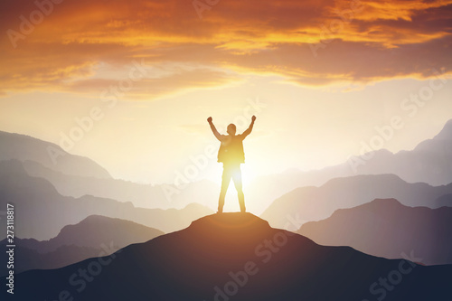 Man standing on edge of mountain feeling victorious with arms up in the air Fototapet