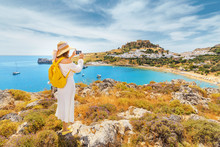 Young Woman Traveler Taking Photo Of Her Smartphone Scenic Landscape Of A Famous Tourist Attraction On Rhodes Island - Lindos Town