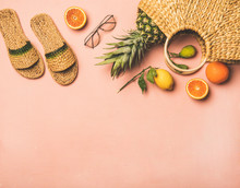 Summer Apparel Items. Flat-lay Of Summer Flip Flops, Sunglasses, Wicker Bag And Fresh Fruits Over Pastel Pink Background, Top View, Copy Space. Summer Beach Vacation Concept