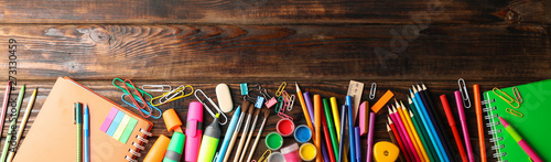 Photo  Flat lay composition with school supplies on wooden background, space for text