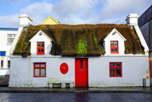 Old Ruined And Abandoned Thatched House With Red Windows And Door