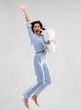 canvas print picture fun, people and bedtime concept - happy young woman full of energy in blue pajama holding pillow and jumping over grey background