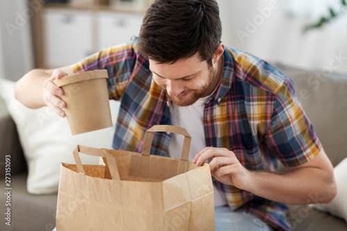 Fotografie, Obraz consumption, eating and people concept - smiling man unpacking takeaway food at