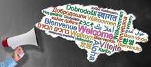 Hand Of Businessman Holding Megaphone Or Bullhorn Against Blackboard With Word WELCOME In Many Different Languages