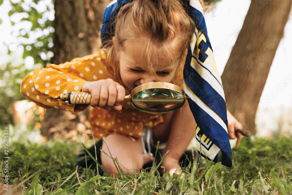Fototapety, obrazy: Image of cute kid with magnifying glass exploring the nature outdoors. Adorable little girl playing in the forest with magnifying glass. Curious child looking through magnifier on a sunny day in park