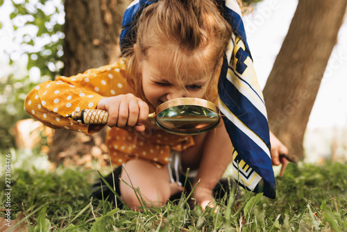 Image of cute kid with magnifying glass exploring the nature outdoors. Adorable little girl playing in the forest with magnifying glass. Curious child looking through magnifier on a sunny day in park - fototapety na wymiar