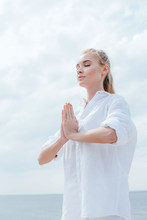 Low Angle View Of Young Woman With Praying Hands Near Sea