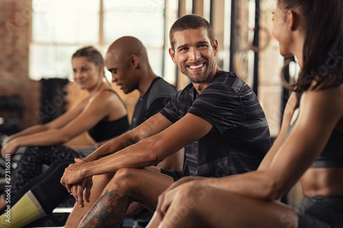 Happy fitness class resting in conversation