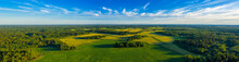 Top Aerial Panoramic View Of Green Fields And Meadows In Summer. Abstract Landscape With Lines Of Fields, Grass, Trees, Sunny Sky And Lush Foliage. Landscape With Drone.