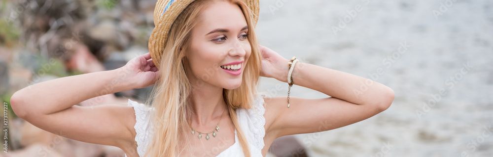 Fototapety, obrazy: panoramic shot of happy young blonde woman touching straw hat