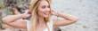 Leinwandbild Motiv panoramic shot of happy young blonde woman touching straw hat