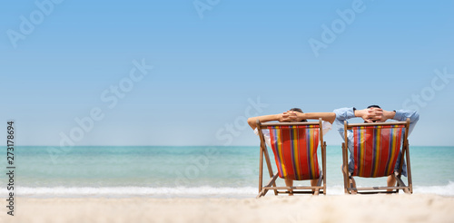 Obraz Couple relaxing on chair beach over sea background. - fototapety do salonu