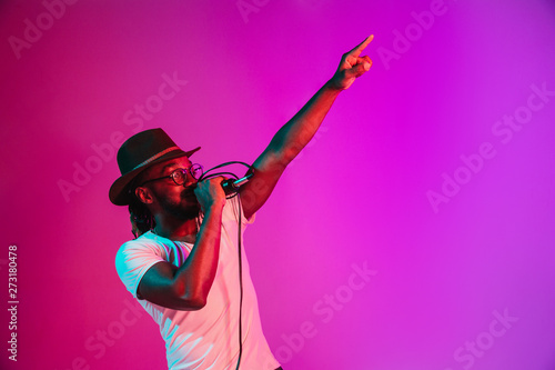 Fotografie, Obraz Young african-american jazz musician with microphone singing a song on purple studio background in trendy neon light