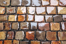 Cobblestone Road, Texture Photographed From Above. Stone Pavement Texture Gray And Brown Color, Wet Pavement. Top View Close Up
