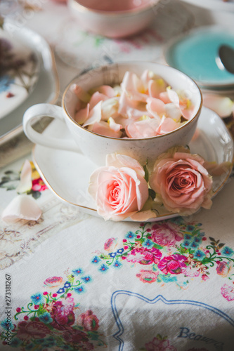 A close up of a cup with tea decorated with roses stands on a served table Wallpaper Mural