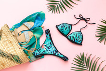 Bikini Swimsuit With Tropical Print, Silver Glitter Flat Sandans, Wicker Beach Bag, Sarong, Tropical Palm Leaves On Pink Background. Overhead View Of Woman's Swimwear And Beach Accessories.